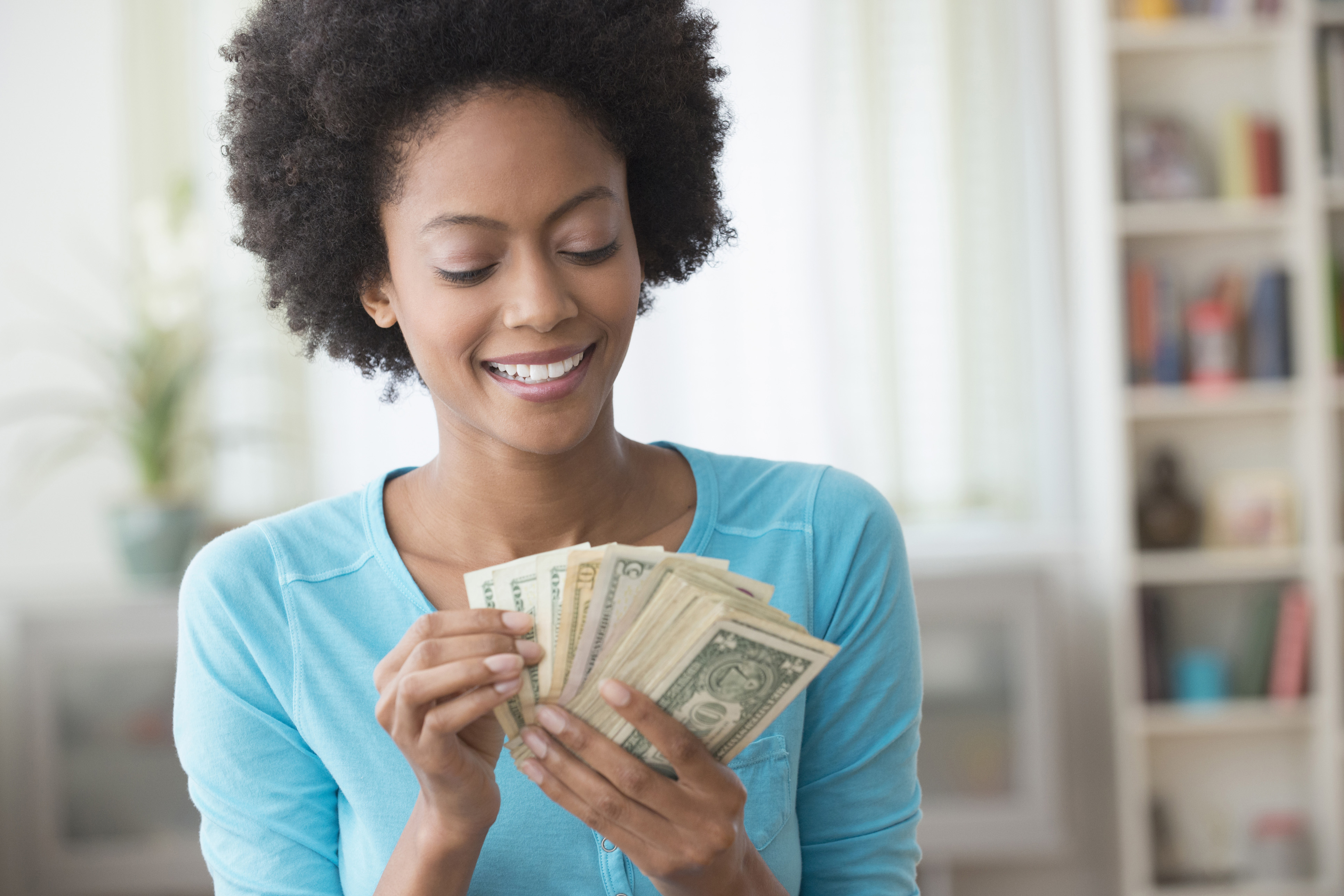 black woman spending money counting money